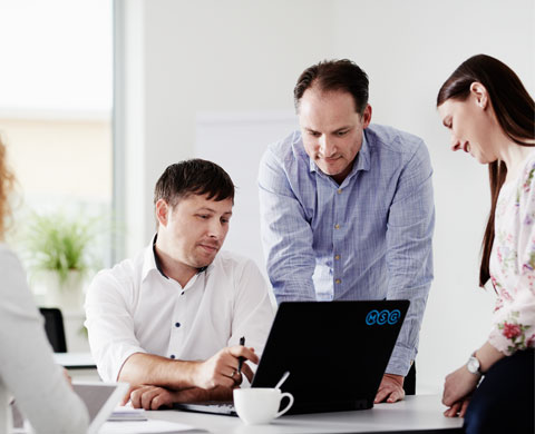 Employees discussing around a laptop