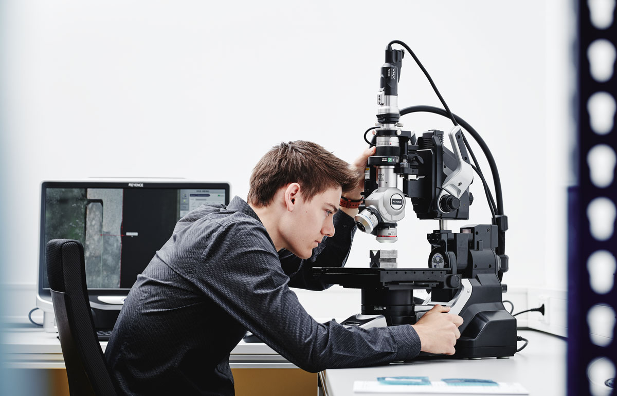 Employee in a dark shirt at a microscope, controlling a part